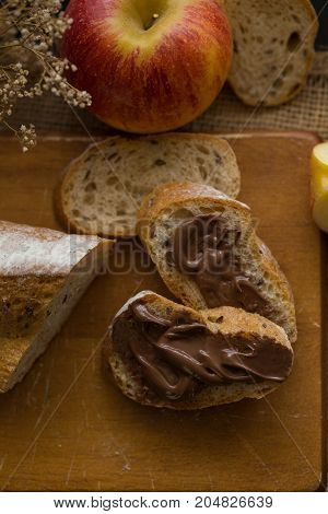 French Bread Baguette Cut On Wooden Board With Knife. With A Chocolate Butter