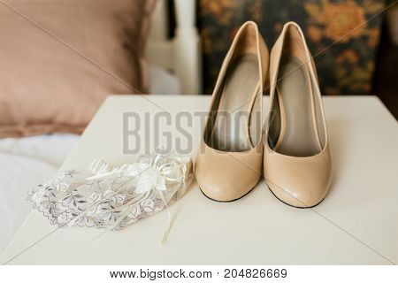 Beige shoes on a heels and lace garter on a white table. Wedding preparation. Artwork, Soft focus