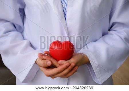 Doctor Hands Holding Red Toy Heart