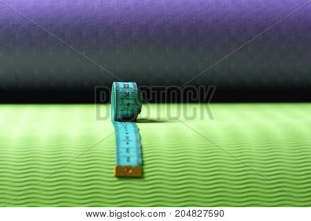 Measuring Tape Roll In Cyan Color On Green Texture Background