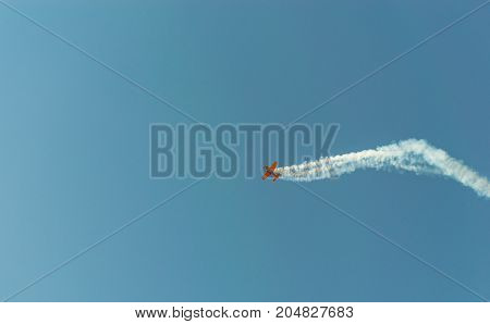 Aerobatic Plane  Leaving A White Smoke Trail In The Blue Sky.
