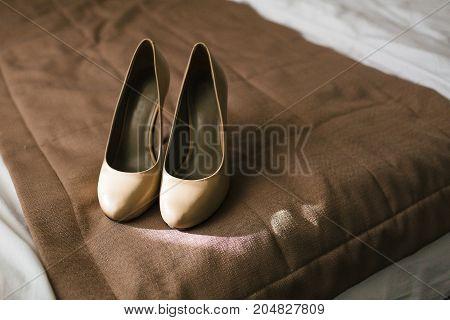 Beige shoes on heels of a bride on a brown textile background. Wedding preparation. Artwork. Soft focus