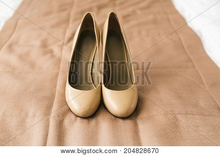 Beige shoes on heels of a bride on a brown textile background. Wedding preparation. Artwork. Soft focus