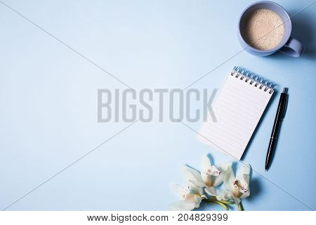 Cup of coffee and notebook with pen and orchid flower on a blue background, top view