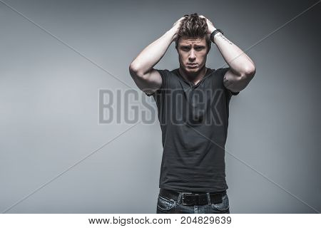 I am in big trouble. Portrait of stressful guy is touching his hair with despair. He is standing and looking at camera with hope. Isolated and copy space