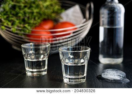 Two glasses and bottle of traditional drink Ouzo or Raki on black dish