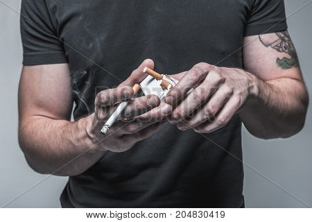Close up of male hands holding burning cigarette and pack with other items