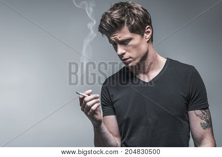 Portrait of sad young man smoking cigarette while suffering from deep depression. He is standing and looking at smoke pensively. Isolated. Copy space in left side