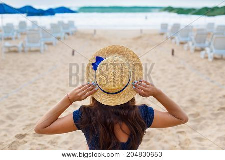 Beautiful girl in a hat sits with her back on a sandy beach.