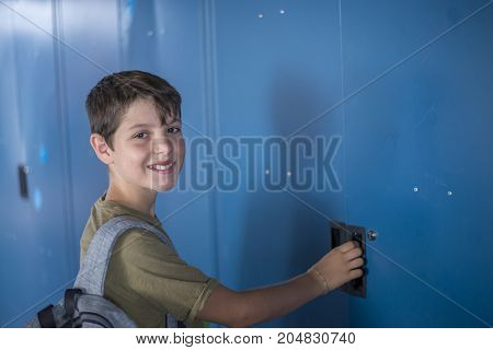 Student standing in front of the blue school lockers