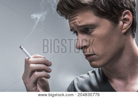 Nicotine addiction concept. Profile of depressed young man looking at burning cigarette with sadness. Isolated on grey background