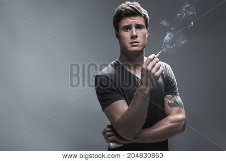 Sad young guy is smoking cigarette to calm himself down. He is looking at camera with frustration while standing. Isolated and copy space. Waist up portrait