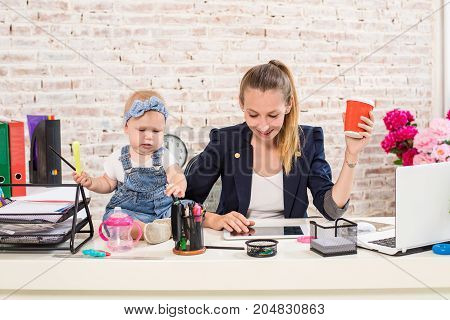 Mom and businesswoman working with laptop computer at home and playing with her baby girl. Horizontal shape, front view, waist up