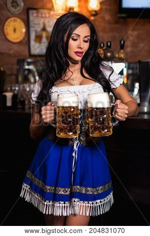 Oktoberfest. Brunette woman holding beer mugs in bar. Sexy woman holding two glasses of beer standing at the bar counter
