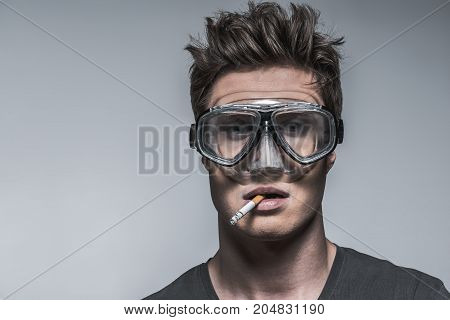 Portrait of thoughtful guy smoking cigarette while keeping item in his mouth. He is wearing diving mask with assurance that it protects him from harm. Isolated and copy space