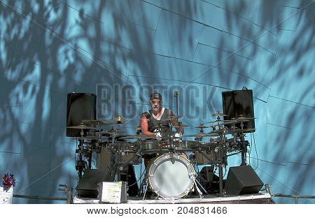 Seattle, Washington - September 5, 2015: Male musician with drumsticks playing drums and cymbals in the park of Seattle, Washington state