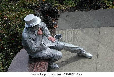 Seattle, Washington - September 5, 2015: An Artist who works as living statue taking break on the bench in Seattle, Washington