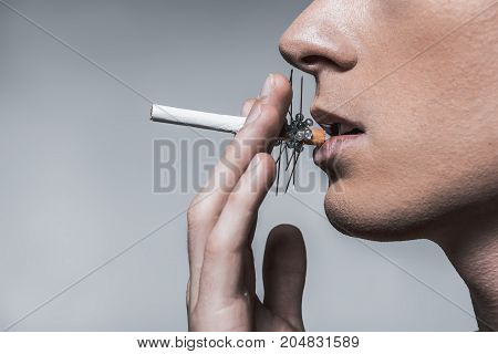 Smoking is dangerous for your health. Close up profile of young man keeping cigarette with needles in his mouth. Isolated and copy space