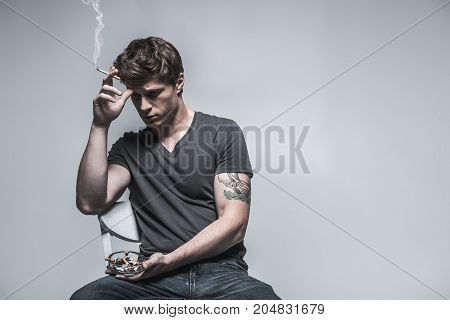 Waist up portrait of depressed young man sitting on chair with cigarette in hand. He is looking down pensively. Isolated. Copy space in right side