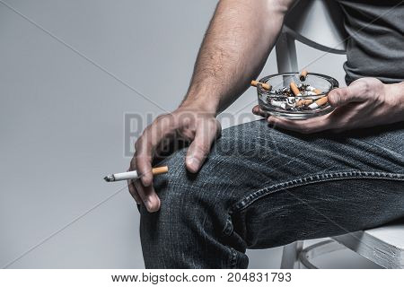 Close up of arm of young guy smoking cigarette. He is sitting and holding glass ash-pot with butts. Isolated and copy space