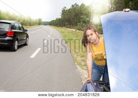Woman Repairing Broken Car On Highway. Girl Stands Near Opened Hood Of Car After An Accident