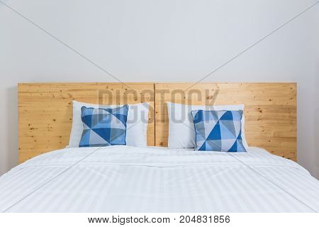empty cozy white bed with blue and white pillows and wooden headboard in white bedroom good for minimalist or young and modern lifestyle concept
