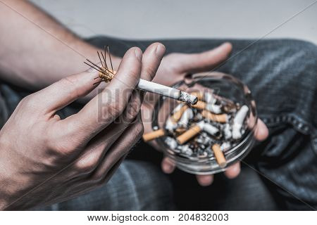 Top view close up focus on human arm holding harmful cigarette while smoking. Man is carrying ashtray with stubs under legs