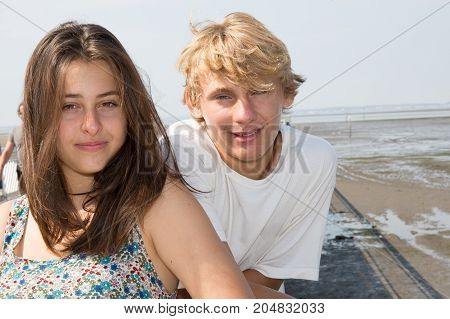 Young Couple In Love Looks At The Camera At The Seaside Beach In Vacation