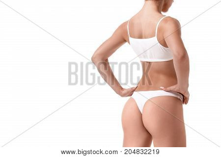 Beautiful healthy fit slim female body on white background. A woman stands with her back on the floor of a turn. Sport. Health. Concept. Copy space plastic surgery