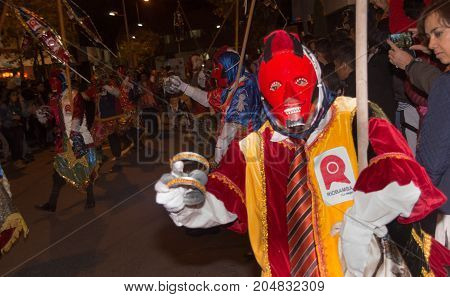 Quito, Ecuador - february 02, 2016: An unidentified man dressed up participating in the Diablada, with a colorful mask in his head while he is dancing in the streets.