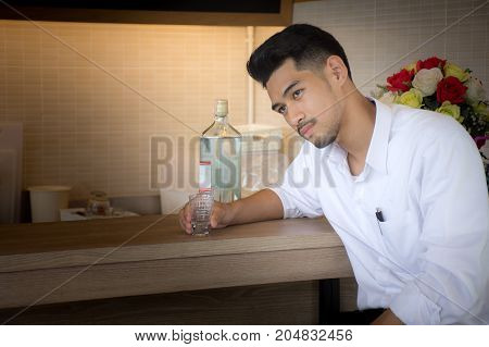 Young businessmen sit and drinking alcohol in the bar,Feeling bad