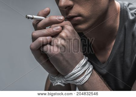 Realizing problems with self-control. Close up of pensive young man smoking cigarette. His hands are tied up with a rope. Isolated and copy space in left side