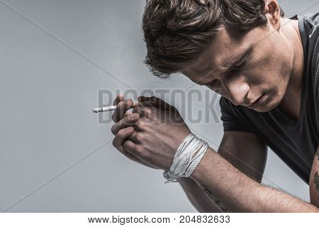 Addicted from nicotine. Depressed young man is holding burning cigarette with tied arms. His eyes are closed with desperation. Isolated and copy space