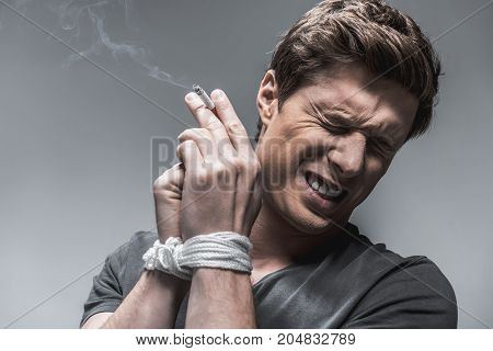 Portrait of frustrated young man has problems with nicotine addiction. He is holding cigarette and closing eyes with aversion. His hands are tied with a rope. Isolated