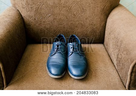 Groom's blue shoes on a brown armchair. Wedding concept. Artwork, soft focus. Top view