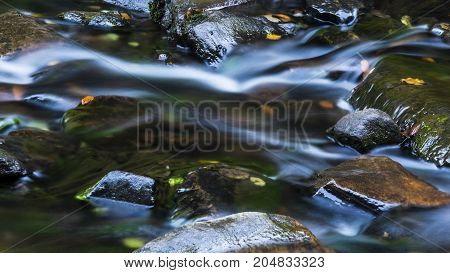 Protracted river flowing over stones in nature.