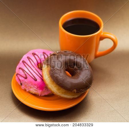 Delicious donut with pink and chocolate glazed over an orange plate, with an orange cup of coffee in a soft brown background.