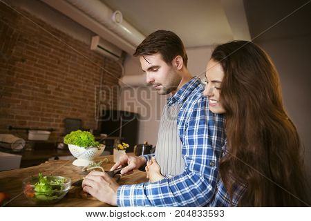 Young smiling couple cooking together at kitchen