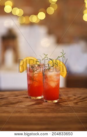 Two red cocktail glasses on wooden bar counter