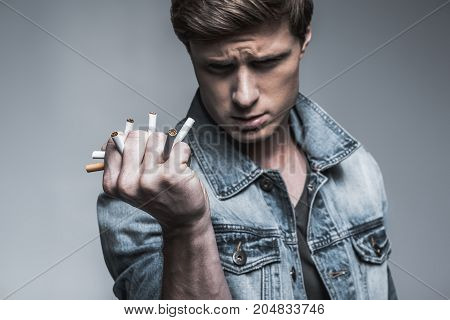 It is time to quit smoking. Confident young guy is clenching cigarettes in his fist. Focus on male arm. Isolated
