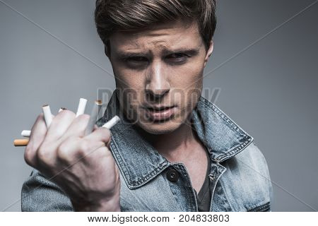 Portrait of stern heavy smoker keeping cigarettes in his fist. He is ready to end up with nicotine. Man is standing and looking at camera with confidence. Isolated