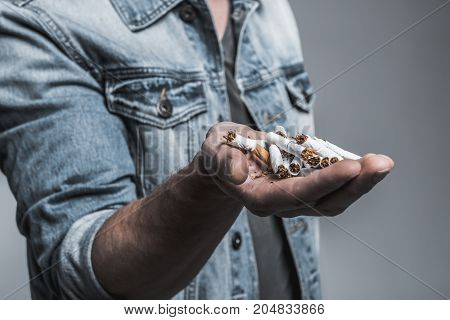Close up of male hand holding crushed cigarettes and showing it to camera. Isolated