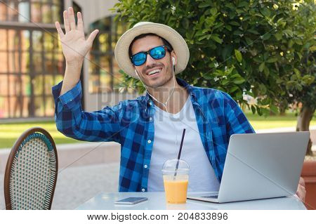 Horizontal Picture Of Young Smiling European Man Spending Time At Table In Outdoor Cafe Working On L