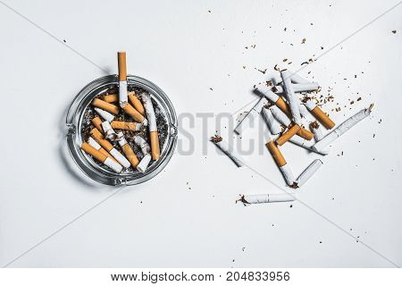 Nicotine is harmful for human health concept. Top view close up of broken cigarettes near ashtray with butts on white table