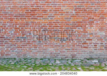 Horizontal Image Of Massive Red Brick Wall Pictured In Sunlight Lined With Thin Stripe Of Green Fres
