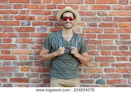 Outdoor Closeup Photo Of Sporty European Guy With Red Brick Background Behind, Looking Straight At C