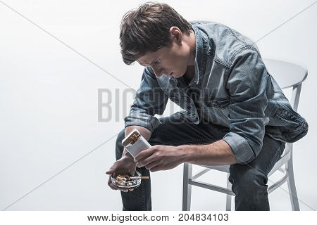Pensive guy is calming down himself by nicotine. He is sitting on chair and looking at ashtray and pack of cigarette. Isolated and copy space