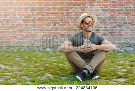 Horizontal Outdoor Picture Of Young Caucasian Guy Sitting On Green Grass And Pebble Pavement With Re