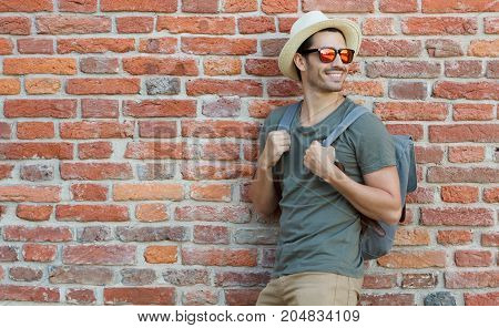 Outdoor Image Of Positive European Male Standing In Casual Clothes With Red Brick Wall Behind, Looki