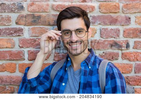 Horizontal Outdoor Closeup Of Young Handsome European Male Standing Against Red Brick Wall With Grey